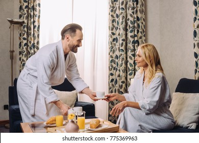 happy mature couple in bathrobes smiling each other while having breakfast together in hotel room