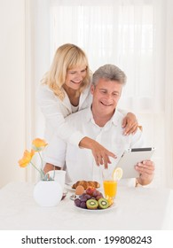 Happy mature couple at the breakfast table using a tablet computer while enjoying a healthy breakfast catching up on their social media contacts online