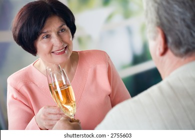A happy mature couple celebrating life event together with champagne