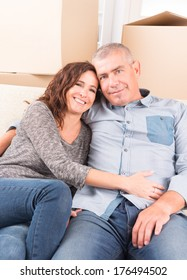 Happy mature couple celebrating their new home sitting together on the sofa just after moving in