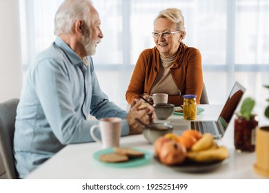 Happy mature couple communicating while having breakfast at dining table.