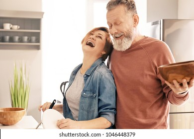 Happy mature couple cooking in kitchen