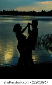 Happy Mature couple dance at twilight near river