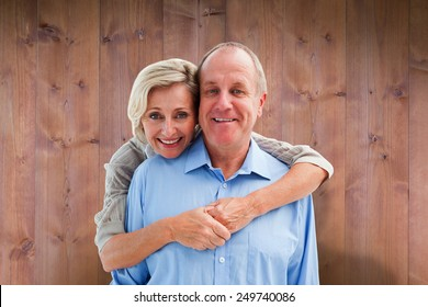 Happy mature couple embracing smiling at camera against wooden planks