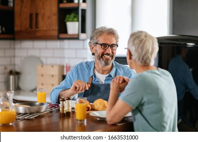 Happy mature couple enjoying a meal together at home