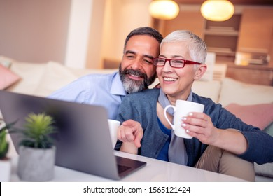 Happy mature couple enjoying in their coffee time in the living room.