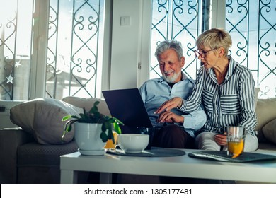 Happy mature couple enjoying together at home and using technology