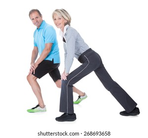 Happy Mature Couple At Gym In Fitness Attire Exercising On White Background