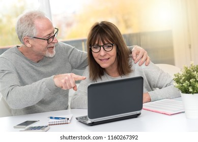 Happy mature couple having an amazing surprise on laptop, light effect