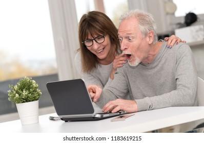 Happy mature couple having an amazing surprise on laptop