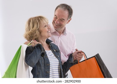 Happy Mature Couple Holding Colored Shopping Bags