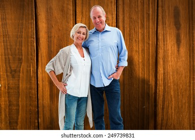Happy mature couple hugging and smiling against overhead of wooden planks