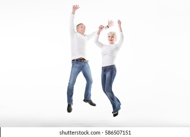 Happy mature couple jumping in studio, smiling.