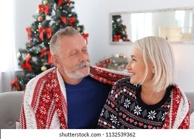 Happy mature couple with plaid at home. Christmas celebration