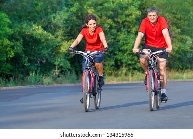 happy mature couple riding a bicycle in park