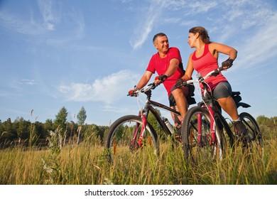 glückliches, reifes Paar, das im grünen Park Fahrrad fährt