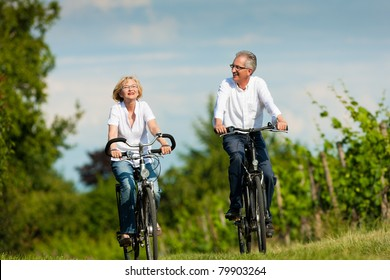 Happy mature couple - senior people, man and woman, already retired - cycling in summer in nature