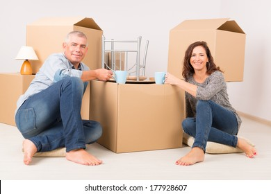 Happy mature couple sitting on the floor in their new home and drinking coffee or tee, boxes in background