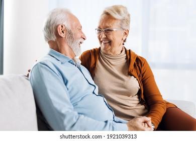 Happy mature couple sitting on sofa and communicating.