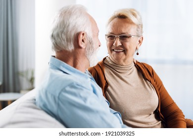 Happy mature couple sitting on a sofa and communicating.