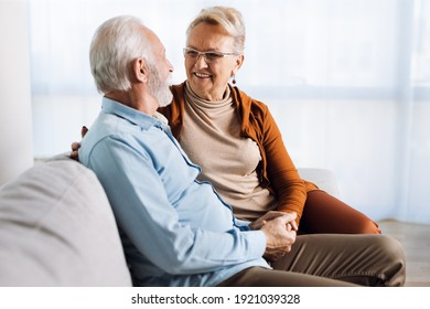 Happy mature couple sitting on a sofa and communicating