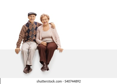 Happy mature couple sitting on a panel isolated on white background