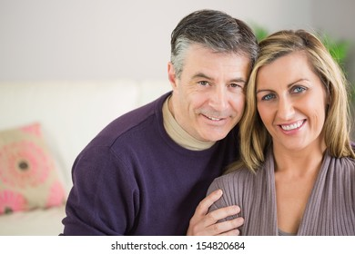 Happy mature couple smiling and looking at camera in a living room