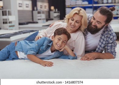 Happy mature couple smiling at their cheerful young son, lying together on orthopedic mattress at furniture store. Lovely family enjoying shopping for furniture at home goods shop