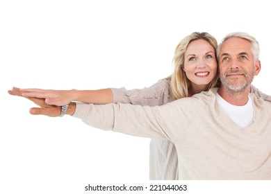 Happy mature couple spreading hands out over white background