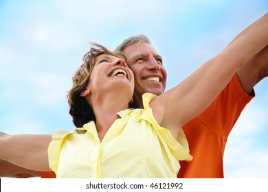 Happy mature couple standing with arms outstretched.