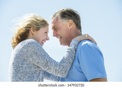 Happy mature couple standing face to face against clear sky