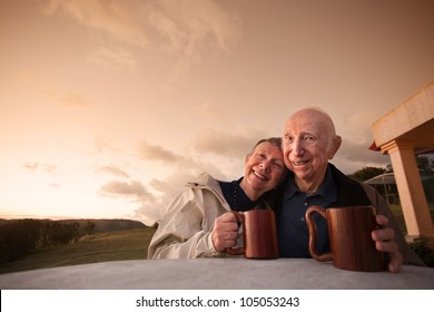 Happy mature couple at table outside with coffee mugs