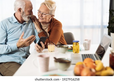 Happy mature couple text messaging on their cell phone at home