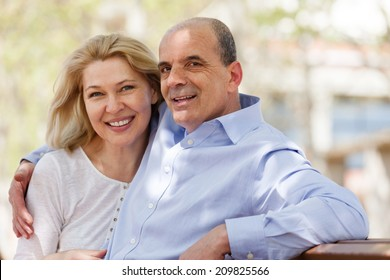 Happy mature couple together in summer park