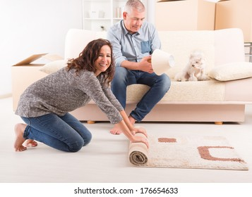 Happy mature couple unpacking in their new home, woman rolling carpet out and man fixing lamp