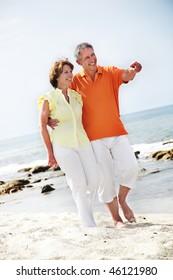Happy mature couple walking along the beach.