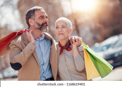 Happy mature couple walking with their shopping bags on a sunny day.