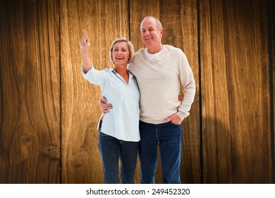 Happy mature couple walking together against wooden table
