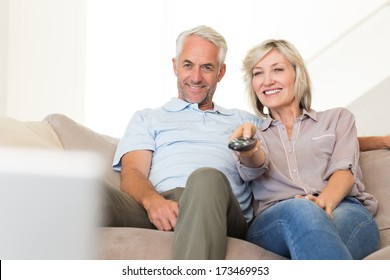 Happy mature couple watching tv on sofa at home