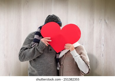 Happy mature couple in winter clothes holding red heart against wooden planks