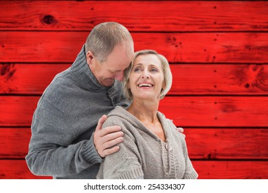 Happy mature couple in winter clothes against red wooden planks