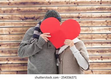 Happy mature couple in winter clothes holding red heart against wooden planks background