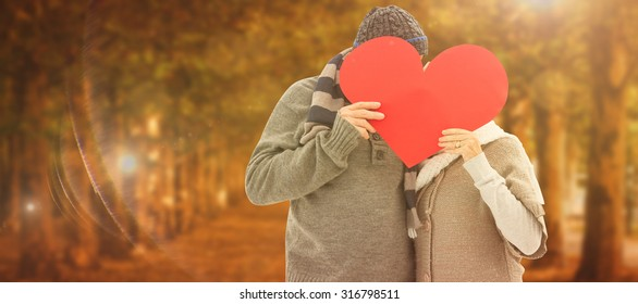 Happy mature couple in winter clothes holding red heart against autumn scene