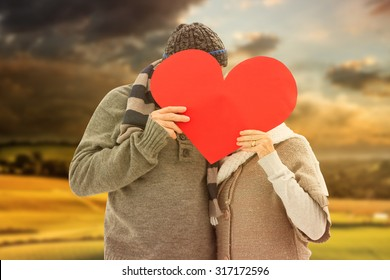 Happy mature couple in winter clothes holding red heart against country scene