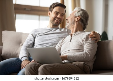 Happy mature dad and adult son sit rest on sofa in living room using modern laptop gadget, millennial man relax on couch at home with elderly father teach browsing wireless Internet on computer