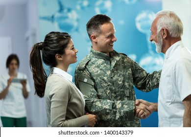 Happy mature doctor handshaking with military officer who came to the appointment with his wife at clinic. Focus is on soldier.