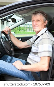 Happy mature driver with car key sitting in own land vehicle