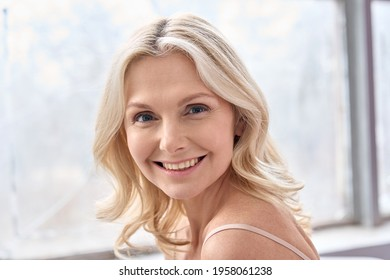 Happy mature elder 50s woman indoors. Closeup headshot portrait of attractive mid age woman looking smiling at camera. Beauty, skin care