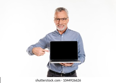 Happy mature in eyeglasses man pointing at blank screen of laptop computer and smiling isolated over white