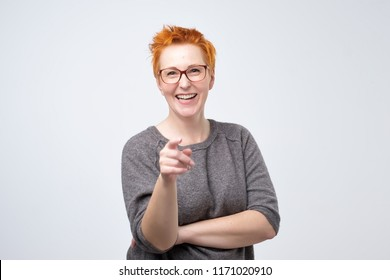 Happy mature fashion woman with red hair posing for the camera while pointing at you. She points to you as the winner